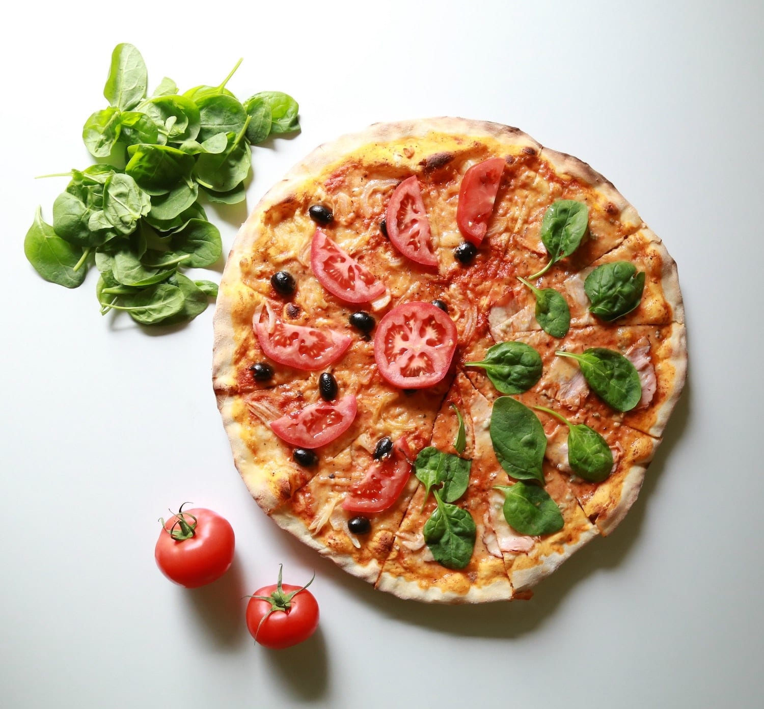 Cheese pizza topped with fresh tomato slices and spinach leaves