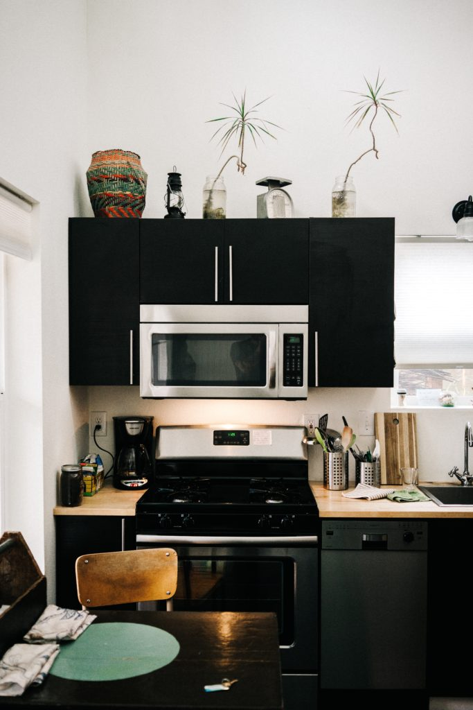 Clean stainless steel microwave and stovetop inside a modern kitchen design.
