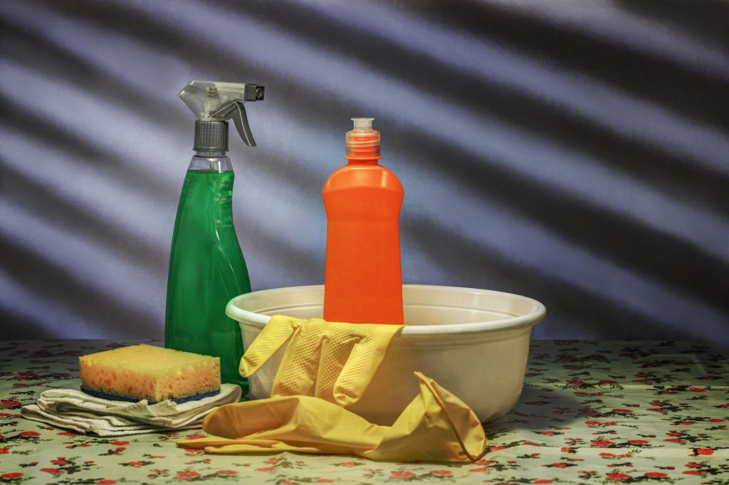 Dish soap, rubber gloves, sponge and spray bottle. Everything you need to clean a microwave with dish soap.