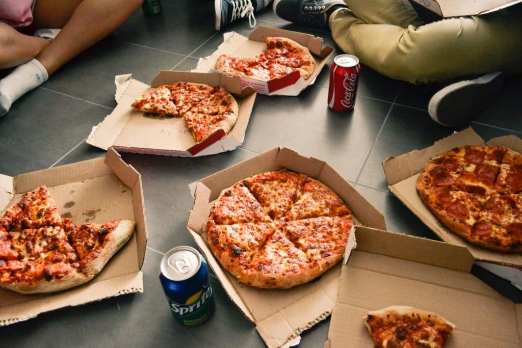 people sitting crossed legged on the floor with five pizzas in pizza boxes.