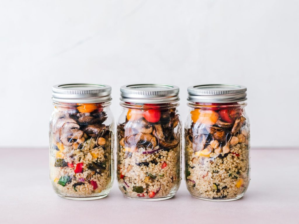 three mason jars filled with a simple meal prep of quinoa and assorted roasted vegetables