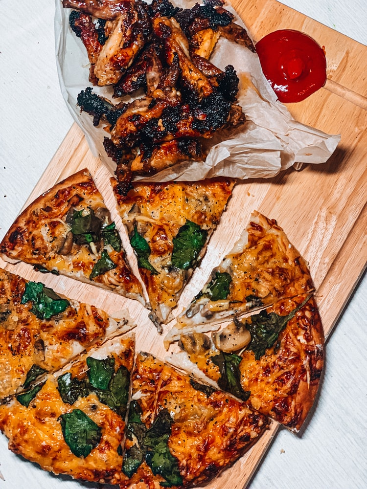 Cold pizza is laying on a cutting board and cut into eight pieces.