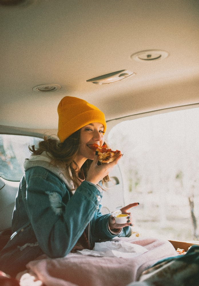 Female sitting inside a car eating cold pizza