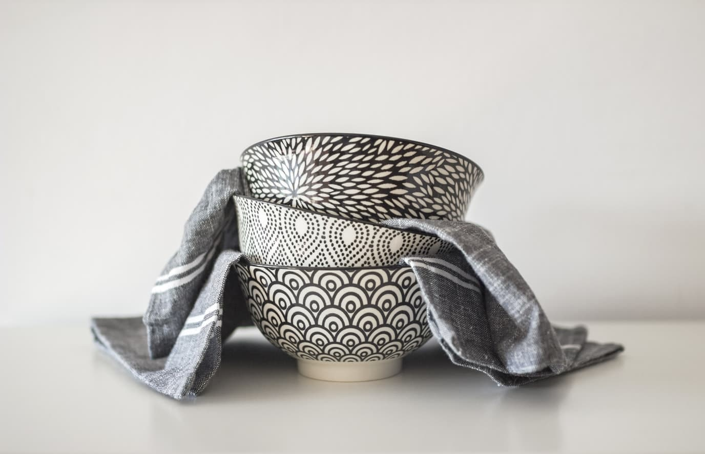 Three decorative soup bowls stacked up on top of each other.